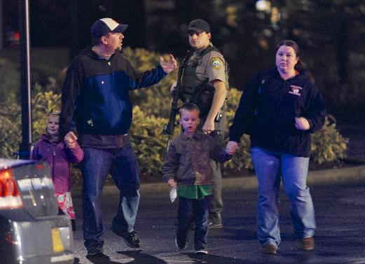 CORRECTS MALL LOCATION - A family leaves the scene of a multiple shooting at Clackamas Town Center Mall in Portland, Ore., Tuesday Dec. 11, 2012. A gunman is dead after opening fire in the Portland, Ore., shopping mall Tuesday, killing two people and wounding another, sheriff's deputies said. (AP Photo/Greg Wahl-Stephens)