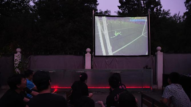 Local football fans watch a World Cup group match projected live on a screen in a Beijing park, on June 13, 2014
