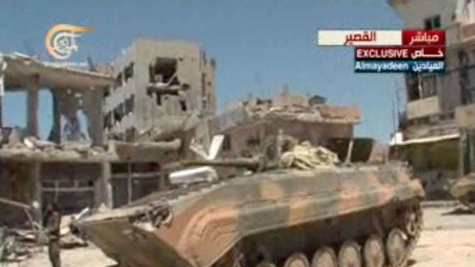 "This image made from video broadcast on Al-Mayadeen Television shows Syrian army tanks in Qusair, Syria, Wednesday, June 5, 2013. The Syrian army triumphantly announced Wednesday the capture of a strategic town near the Lebanese border, telling the nation it has ""cleansed"" the rebel-held Qusair of ""terrorists"" fighting President Bashar Assad's troops. The capture of the town, which lies close to the Lebanese border, solidifies some of the regime's recent gains on the ground that have shifted the balance of power in Assad's favor in the Syrian civil war. (AP Photo/Al-Mayadeen Television via AP video)"
