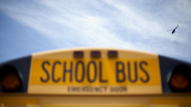 A police helicopter hovers over a school bus as it drops off children outside a subdivision Wednesday, May 16, 2012, in Hampton, Ga. Police in an Atlanta suburb are escorting school buses and guarding students at bus stops after a man aimed a rifle at a bus with children on board and dropped a notebook that listed bus numbers. (AP Photo/David Goldman)