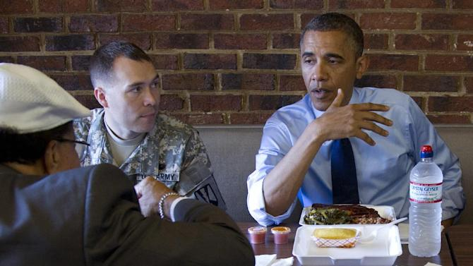 President Barack Obama visits a Kenny's BBQ restaurant with Army First Lt. William Edwards, a 2012 Military Fatherhood Award Winner, second from left, and Nurney Mason owner of Mason's Barber Shop, left back to camera,  Wednesday, June 13, 2012, in Washington. (AP Photo/Carolyn Kaster)