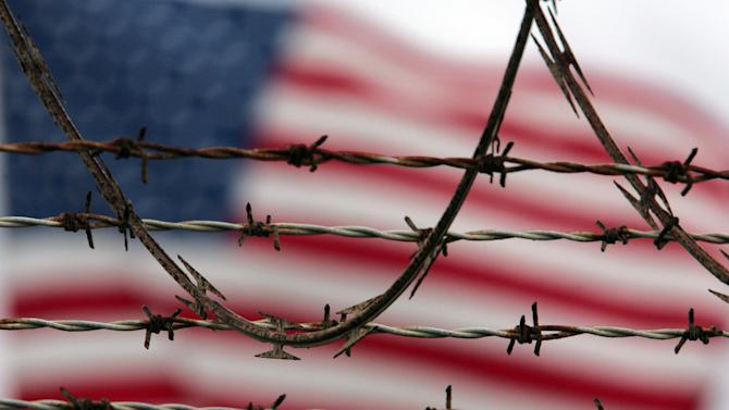 ** FILE ** In this Oct. 10, 2007 file photo, reviewed by the U.S. Military, an American flag flies behind the barbed and razor-wire at the Camp Delta detention facility, at Guantanamo Bay U.S. Naval Base, Cuba. The Pentagon said Saturday that four Afghans from the Guantanamo Bay detention center have been returned to their home country in what U.S. officials are citing as a sign of their confidence in new Afghan President Ashraf Ghani.  (AP Photo/Brennan Linsley)
