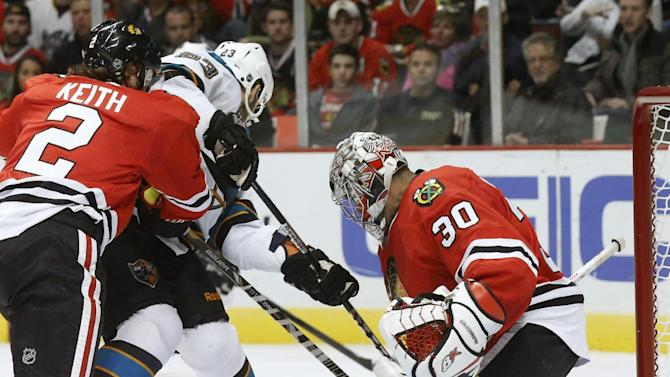Chicago Blackhawks goalie Ray Emery (30) saves a rebound attempt by San Jose Sharks center Scott Gomez (23) as Duncan Keith (2) also defends during the first period of an NHL hockey game Friday, Feb. 15, 2013, in Chicago. (AP Photo/Charles Rex Arbogast)