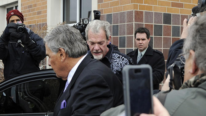 Attorney James Voyles, center left, and Indianapolis Colts owner Jim Irsay, center right, leave the Hamilton County Jail in Indianapolis, Monday, March 17, 2014. Irsay was released from jail Monday after being held overnight following a traffic stop in which police said he failed sobriety tests and had multiple prescription drugs inside his vehicle. Irsay was pulled over late Sunday after he was spotted driving slowly near his home in suburban Carmel, stopping in the roadway and failing to use a turn signal. (AP Photo/Alan Petersime)