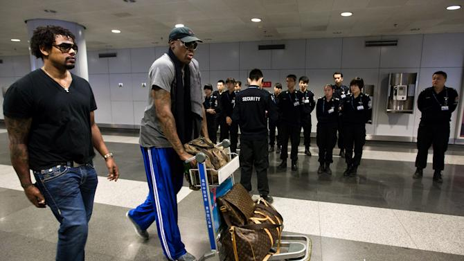 Former NBA star Dennis Rodman, center, pushes his luggage pass through a group of Chinese security officers as he makes his way to the check in counter at the departure hall of Beijing Capital International Airport in Beijing Tuesday, Feb. 26, 2013. Rodman, and three members of the Harlem Globetrotters basketball team, a VICE correspondent and a production crew from the company are visiting North Korea to shoot footage for a new TV show set to air on HBO in early April, VICE told The Associated Press in an exclusive interview before the group's departure from Beijing. (AP Photo/Andy Wong)