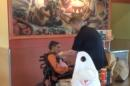 This image taken from video shot by Dr. David Jones, shows restaurant worker Ridge Quarles feeding a disabled woman her food at the Qdoba restaurant in Louisville, Ky., on Wednesday, April 29, 2015. The video of Quarles doing the good deed has been shared widely online. (Dr. David Jones via AP)