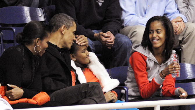 FILE - In this Nov. 27, 2010, file photo, file photo President Barack Obama kisses his daughter Sasha on the head while his other daughter Malia, right, and first lady Michelle Obama look during an NCAA college basketball game in Washington between Howard University and the Oregon State team coached by the first lady's brother Craig Robinson. Obama likes to talk about his kids. What parent doesn't? But he's the president, and he brings up his daughters to explain his thinking on all sorts of combustible national issues, from the rescue of an American aid worker from Somali pirates to the touchy subject of public access to emergency contraception. (AP Photo/Cliff Owen, File)