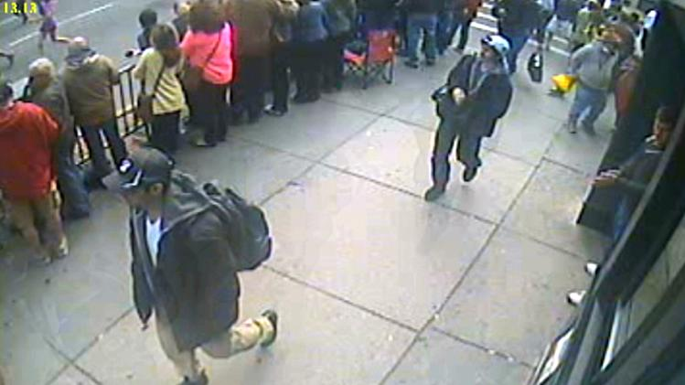 This frame grab from a video released by the FBI on Thursday, April 18, 2013, shows what the FBI are calling suspect number 1, front, in black cap, and suspect number 2, in white cap, back right, walking near each other through the crowd in Boston on Monday, April 15, 2013, before the explosions at the Boston Marathon. (AP Photo/FBI)