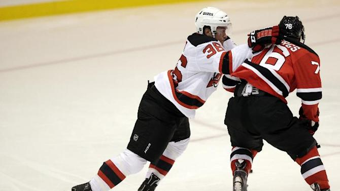 Joe Faust, left, practices defending without a stick against Roberts Lipsbergs during the New Jersey Devils' rookies NHL hockey camp, Tuesday, July 15, 2014, in Newark, N.J