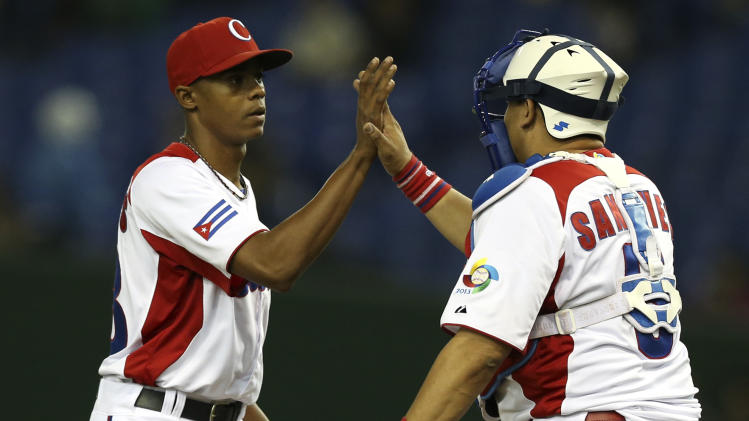 Cuba's closer Raciel Iglesias, left, celebrates with catcher Erier Sanchez after beating Taiwan in their World Baseball Classic second round game at Tokyo Dome in Tokyo, Saturday, March 9, 2013. The game was called in the top of the seventh inning with a score of 14-0. (AP Photo/Toru Takahashi)
