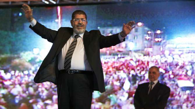 """FILE - In this Sunday, May 20, 2012 file photo, the Muslim Brotherhood's presidential candidate Mohammed Morsi hold a rally in Cairo, Egypt. A statement on the Egyptian president's office's Twitter account has quoted Mohammed Morsi as calling military measures """"a full coup."""" The denouncement was posted shortly after the Egyptian military announced it was ousting Morsi, who was Egypt's first freely elected leader but drew ire with his Islamist leanings. The military says it has replaced him with the chief justice of the Supreme constitutional Court, called for early presidential election and suspended the Islamist-backed constitution.(AP Photo/Fredrik Persson, File)"""