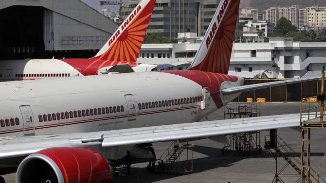 A man stands under a parked Air India aircraft at the Chhatrapati Shivaji international airport in Mumbai, India, Friday, May 11, 2012. Hundreds of passengers have been stranded in India after Air India canceled around 20 international flights due to a strike by pilots. (AP Photo/Rajanish Kakade)