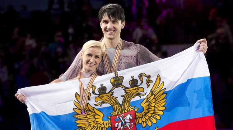 Gold medalists Tatiana Volosozhar and Maxim Trankov from Russia, pose with their medals and flag during victory ceremonies in the pairs competition at the World Figure Skating Championships Friday, March 15, 2013 in London, Ontario. (AP Photo/The Canadian Press, Paul Chiasson)