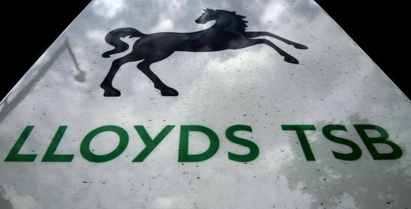 File photogrpah shows the sky reflected in a sign at a Lloyds TSB bank in London