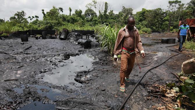 In this photo taken Saturday, May 18, 2013, men walk past an abandoned illegal refinery at the creeks of Bayelsa, Nigeria. The first drops of crude float in the languid muddy currents of Nigeria's oil-rich southern delta, then slowly grow into the splatter of massive crime scene. Oil thefts, long a problem in the Niger Delta, are growing at an ever-faster rate despite government officials and international companies offering increasingly dire warnings about the effect on Nigeria's crude production. Some 200,000 barrels a day representing about 10 percent of Nigeria's production are siphoned off pipelines crisscrossing the region. (AP Photo/Sunday Alamba)