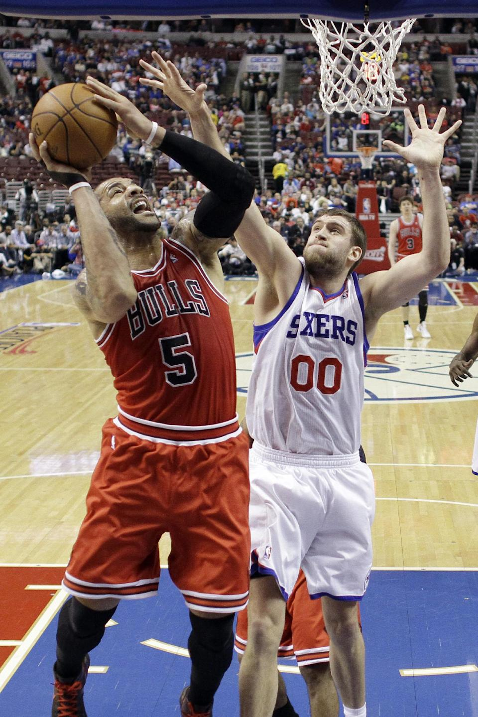 Chicago Bulls' Carlos Boozer (5) shoots as Philadelphia 76ers' Spencer Hawes (00) defends in the first half of Game 6 in an NBA basketball first-round playoff series, Thursday, May 10, 2012, in Philadelphia. (AP Photo/Matt Slocum)