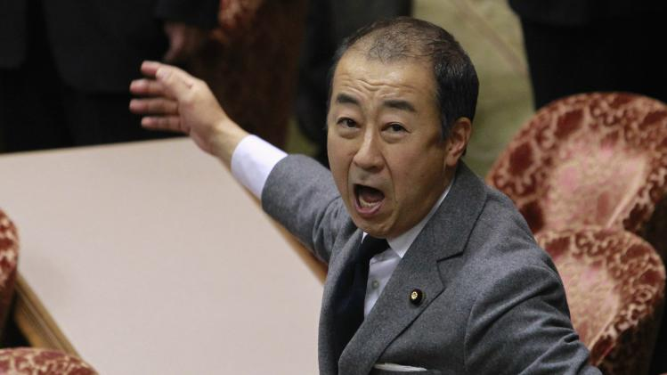 Esaki, a lawmaker of opposition DPJ, reacts as he looks at the media and observers after a vote on a state secrets act, at the Upper House Special Committee on National Security, at parliament in Tokyo