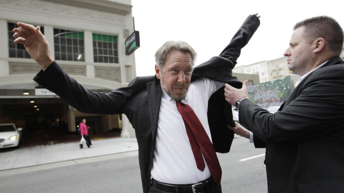 Oracle CEO Larry Ellison, left, puts on his suit as arrives for a court appearance at a federal building in San Francisco, Tuesday, April 17, 2012. Oracle intends to rely heavily on Google's own internal emails to prove Google's top executives knew they were stealing a popular piece of technology to build the Android software that now powers more than 300 million smart phones and tablet computers. (AP Photo/Paul Sakuma)