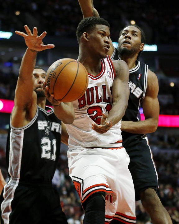 Chicago Bulls shooting guard Jimmy Butler (21) passes in front of San Antonio Spurs power forward Tim Duncan, left, and small forward Kawhi Leonard, right, during the second half of an NBA basketball