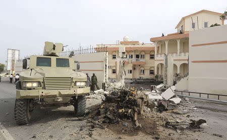 Somali government forces drive their APC at the scene of a suicide car explosion in front of the SYL hotel in Mogadishu