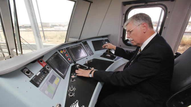 In this photo taken Saturday, May 11, 2013, Joseph Boardman, Amtrak President and CEO, left, looks over the controls of the new Amtrak Cities Sprinter Locomotive that was built by Siemens Rail Systems in Sacramento, Calif.  The new electric locomotive will run on the Northeast intercity rail lines and  replace Amtrak locomotives that have been in service for 20 to 30 years.(AP Photo/Rich Pedroncelli)