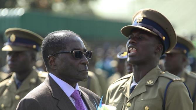 Police officers are on parade as President Robert Mugabe inspects the guard of honour, at a police pass-out parade in Harare, Thursday, June, 13, 2013. Mugabe has proclaimed July 31 as the date at which general elections will be held in the Southern African nation. (AP Photo/Tsvangirayi Mukwazhi)
