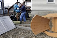 Ed Plieninger cleans debris from Superstorm Sandy that washed into his yard on Cedar Bonnet Island, N.J., Saturday, Nov. 3, 2012. Frustration is setting in for some New Jersey residents who are still without power and running low on food. Some residents say too much attention is being paid to the Shore and not enough to working people who are hurting. (AP Photo/Patrick Semansky)