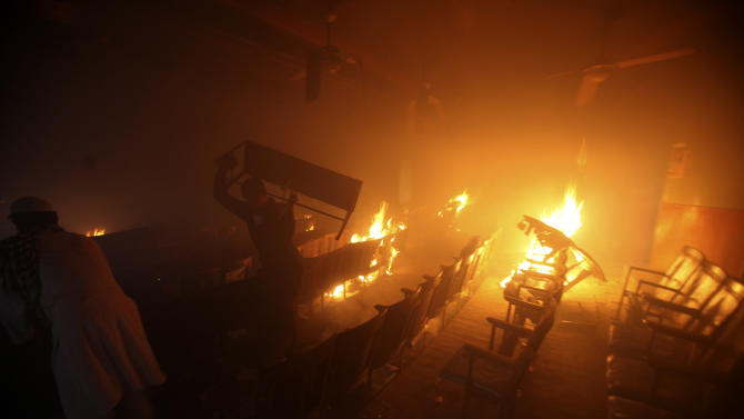 "Protesters torch a cinema in Peshawar, Pakistan on Friday, Sept 21, 2012. Tens of thousands protested around the country against an anti-Muslim film after the government encouraged peaceful protests and declared a national holiday ? ""Love for the Prophet Day."" Demonstrations turned violent and over a dozen people were killed, including a driver for a Pakistani television station, who died after police opened fire on rioters torching a cinema in the northwest city of Peshawar. (AP Photo/Mohammad Sajjad)"