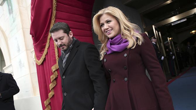 """FILE - In this Monday, Jan. 21, 2013 photo, singer Kelly Clarkson and Brandon Blackstock arrive on the West Front of the Capitol in Washington, for President Barack Obama's ceremonial swearing-in ceremony during the 57th Presidential Inauguration. Clarkson and her music manager Blackstock have gotten married. Clarkson tweeted a photo Monday, Oct. 21, 2013, in her wedding gown next to Blackstock. She wrote: """"I'm officially Mrs. Blackstock."""" (AP Photo/Win McNamee, Pool, File)"""