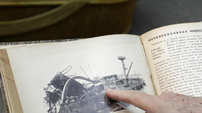 In this Tuesday, Feb. 12, 2013 photo, city historian Eusebio Leal shows a book with a photograph of the USS Maine after it exploded and sank in the Havana Harbor, at his office in Havana, Cuba. It was a little before 10 p.m. that February night in 1898 when a fiery explosion roiled the normally calm waters of Havana Harbor, blowing out windows in the city and sinking the USS Maine to the bottom of the bay, just the mast and some twisted metal wreckage left to poke above the waves. (AP Photo/Franklin Reyes)