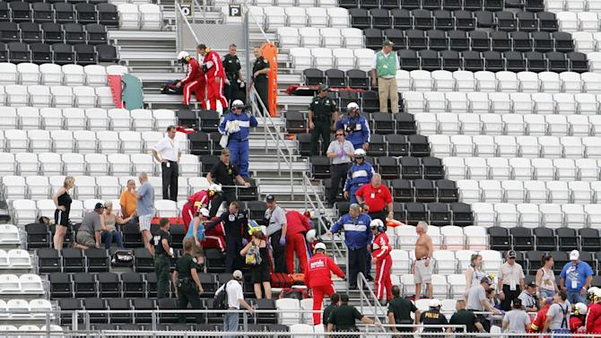 Emergency workers check on fans in the stands after a crash on the final lap of the NASCAR Nationwide Series auto race Saturday, Feb. 23, 2013, at Daytona International Speedway in Daytona Beach, Fla. At least 11 fans were injured when large chunks of debris, including a tire, sailed into the grandstands when a car flew into the fence. (AP Photo/David Graham)