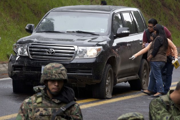 An armored U.S. Embassy vehicle attacked by unknown assailants on the highway leading to the city of Cuernavaca, is checked by security personal near Tres Marias, Mexico, Friday, Aug. 24, 2012. Two U.