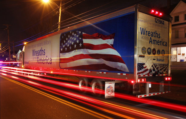Traffic moves by a parked convoy of tractor-trailers carrying wreaths, Sunday, Dec. 4, 2011, in Portland, Maine. Morrill Worcester, of Harrington, Maine, has arranged for up to 100,000 wreaths to be placed on grave sites at Arlington Cemetery Dec. 10 in his biggest wreath-laying undertaking yet. (AP Photo/Robert F. Bukaty)