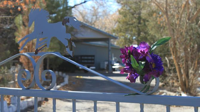 A bouquet of flowers adorns the entrance to a home on Monday, Jan. 21, 2013, where a couple and their three young children were found shot to death south of Albuquerque, N.M. The couple's 15-year-old son, Nehemiah Griego, is facing counts of murder and child abuse in connection with the shootings. (AP Photo/Susan Montoya Bryan)