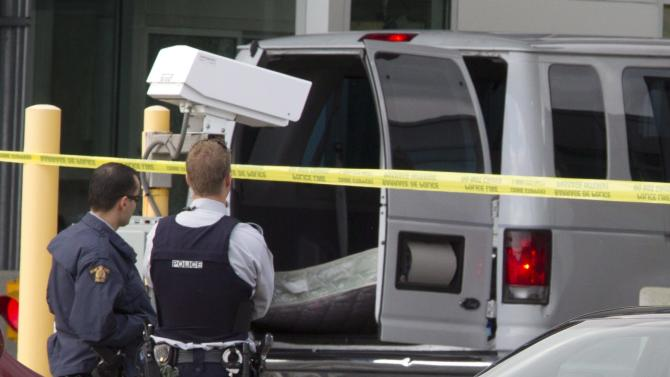 Police investigate a van at the scene of a shooting at the Blaine, Wash./Surrey, British Columbia border crossing, Tuesday, Oct. 16, 2012, in Surrey. Royal Canadian Mounted Police Cpl. Bert Paquet says a border officer was in her booth when she was shot in the neck at about 2 p.m. Tuesday by a man trying to enter Canada in the van bearing Washington state plates. (AP Photo/The Canadian Press, Jonathan Hayward)