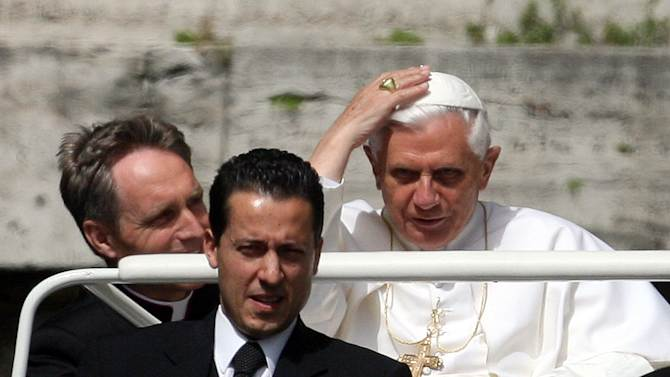 """FILE - In this May 31, 2006 file photo, Pope Benedict XVI arrives with his butler, Paolo Gabriele, foreground, and his personal secretary Georg Gaenswein, left, in St. Peter's Square at the Vatican. When Benedict steps down on Feb. 28, 2013, his reputation as a brilliant theologian will remain intact. But some major scandals shook the Vatican during Benedict's pontificate. Paolo Gabriele was convicted and sentenced to prison after stealing the pope's personal correspondence and leaking the documents to a journalist. Gabriele said he thought the pope wasn't being informed of the """"evil and corruption"""" in the Vatican. Benedict later pardoned him. (AP Photo/Alessandra Tarantino, File)"""