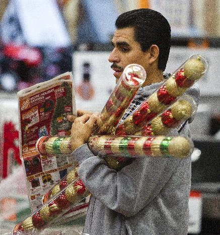 FILE-In this  Friday, Nov. 25, 2011, file photo, Sergio Lira, of Phoenix, holds Christmas bulbs as he shops at the Home Depot in Phoenix. Americans are expected to spend more during what's traditionally the busiest shopping season of 2012, but they're not exactly ready to shop 'til they drop like they have been in the past two years. The National Retail Federation, the nation's largest retail trade group, said Tuesday, Oct. 2, 2012, that it expects sales during the winter holiday shopping period in November and December to rise 4.1 percent this year. (AP Photo/Arizona Republic, Tom Tingle) MARICOPA COUNTY, NO SALES