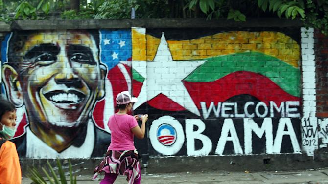 """A woman takes a photo of a wall painting created by Myanmar graffiti artists to welcome U.S. President Barack Obama on a street in Yangon, Myanmar, Saturday, Nov. 17, 2012. Obama will visit Myanmar on Monday, in a first for a sitting U.S. president. White House officials on Thursday said he will use his visit """"to lock down progress and to push on areas where progress is urgently needed"""" — most notably freeing political prisoners and ending ethnic tensions in the western state of Rakhine and the northern state of Kachin. Obama's stop in Myanmar, scheduled to last about six hours, is the centerpiece of his first foreign tour since winning re-election. (AP Photo)"""