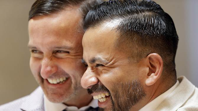 Peter Madril, left, and Monte Young embrace after getting married at City Hall in San Francisco, Saturday, June 29, 2013. Dozens of gay couples waited excitedly Saturday outside of San Francisco's City Hall as clerks resumed issuing same-sex marriage licenses, one day after a federal appeals court cleared the way for the state of California to immediately lift a 4 ½ year freeze. Big crowds were expected from across the state as long lines had already stretched down the lobby shortly after 9 a.m. City officials decided to hold weekend hours and let couples tie the knot as San Francisco is also celebrating its annual Pride weekend expected to draw as many as 1 million people. (AP Photo/Marcio Jose Sanchez)