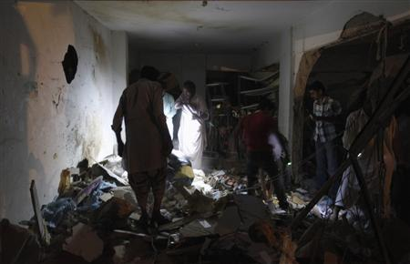 Residents search for their belongings after a bomb blast in a residential area in Karachi