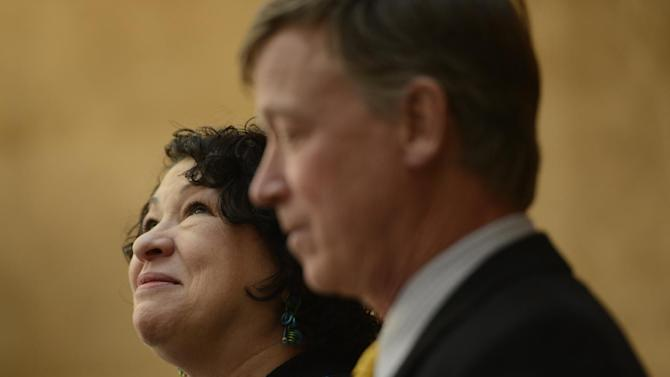 FILE - In this Thursday, May 2, 2013 file photo, Supreme Court Justice Sonia Sotomayor, next to Colorado Governor John Hickenlooper, looks up at the crowd during a dedication of the new Ralph L. Carr Colorado Judicial Center in Denver. On Sunday, May 5, 2013, Sotomayor, the first Hispanic justice on the nation's highest court, spoke at Cooper Union, a private college in Manhattan's East Village where Abraham Lincoln once gave a speech against slavery. (AP Photo/The Denver Post, RJ Sangosti, Pool, File)