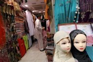 A store employee folds clothes inside a shop at a traditional market in Dubai. To address the rising costs of marriage, the government has ordered that each Emirati man who wants to marry be given $19,000 -- but on condition that it is his first marriage