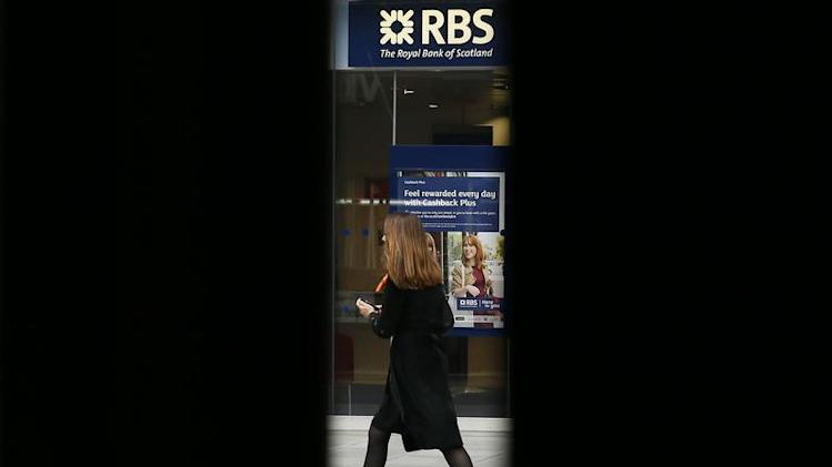 A woman is seen through scaffolding as she walks past a branch of the Royal Bank of Scotland in London