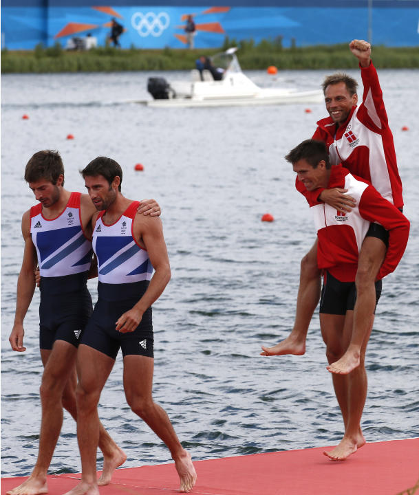 Gold medallists Rasmussen and Quist of Denmark celebrate next to silver medallists Purchase and Hunter of Britain after competing in the men's lightweight double sculls final during the London 2012 Ol