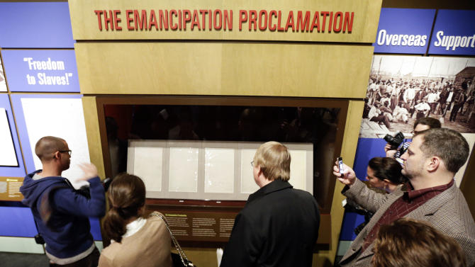 People pass by The Emancipation Proclamation during a special viewing at the Tennessee State Museum on Monday, Feb. 11, 2013, in Nashville, Tenn. The document is at the museum in conjunction with an exhibit titled Discovering the Civil War from the National Archives. The papers will only be on view for 72 hours, which is being spread over seven days. It is scheduled to go on view to the public Tuesday, Feb. 12, and close Monday, Feb. 18. (AP Photo/Mark Humphrey)