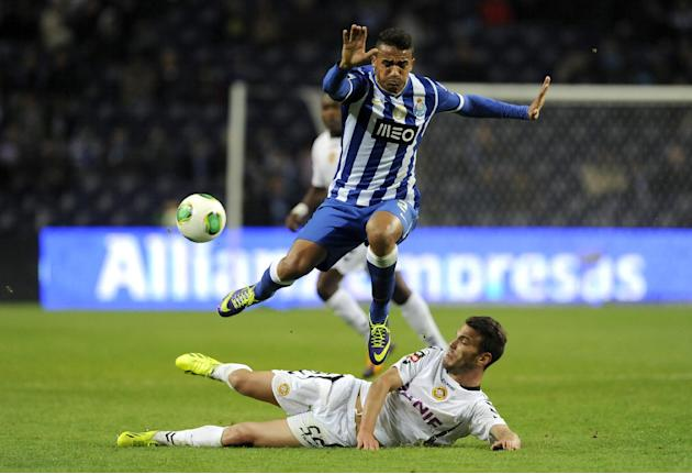 Nacional's Nuno Sequeira, on the pitch, clears the ball from FC Porto's Danilo Silva, from Brazil, in a Portuguese League soccer match at the Dragao stadium in Porto, Portugal, Saturday, Nov. 23, 2013