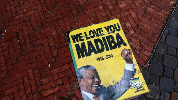 A placard showing a picture of late South African president Mandela is seen on a pavement in Johannesburg