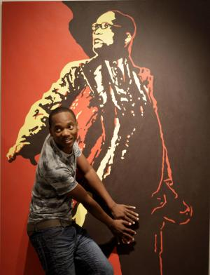"""File -  In this Friday, May 18, 2012 file photo a visitor to the Goodman Gallery in Johannesburg holds his hands over what could be a codpiece accentuating the genitals on a painting entitled """"The Spear"""" depicting President Jacob Zuma, by South African artist Brett Murray. South Africa's Film and Publication Board on Wednesday Oct. 10 2012, declassified the  painting, which outraged supporters of  Zuma when it was displayed,  is no longer deemed offense to public taste. (AP Photo / Denis Farrell, file)"""