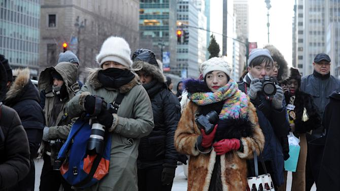 Street photographers brave the cold to photograph guests arriving to the Alexander Wang Fall 2016 show during Fashion Week, Saturday, Feb. 13, 2016, in New York. With temperatures continuing to drop throughout the day Saturday, Mayor Bill de Blasio urged New Yorkers to stay safe and warm by limiting time outdoors, reporting heat and hot water conditions to 311, and checking in on vulnerable friends, relatives and neighbors.  (AP Photo/Diane Bondareff)