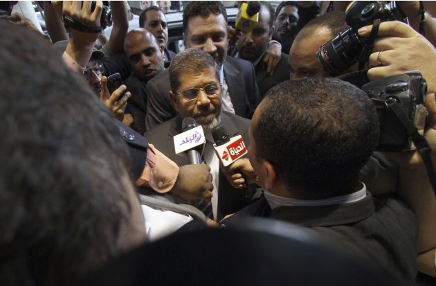 Mohammed Morsi, the Muslim Brotherhood's presidential candidate, is surrounded by reporters in Cairo, Egypt, Saturday, May 26, 2012. Results from the first round of voting have shown that the Muslim B